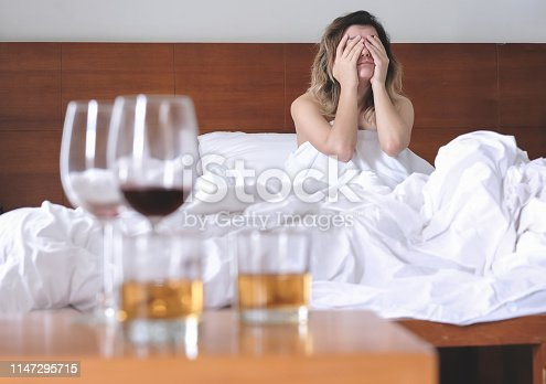 Young exhausted and wasted woman waking up suffering headache and hangover after drinking alcohol lying on bed sick and miserable still drunk