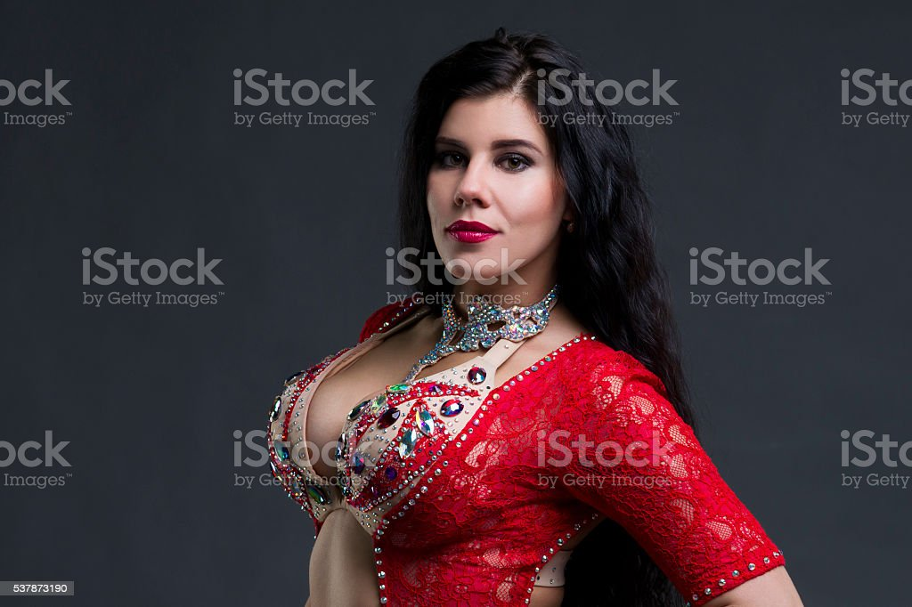 Young exotic eastern women in red dress on gray background stock photo
