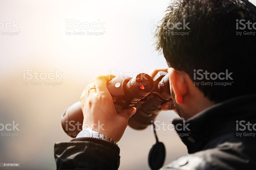 Young explorer looking through binoculars stock photo