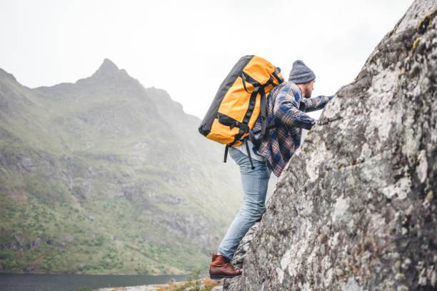 Junge Extrem-Lifestyle-Kletterer mit professionellem Rucksack klettern auf den Felsen. Aktiver furchtloser Profi-Tourist schwärmen auf Bergen – Foto