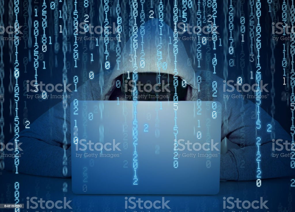 Young faceless man hacker working on a laptop on a binary code background stock photo