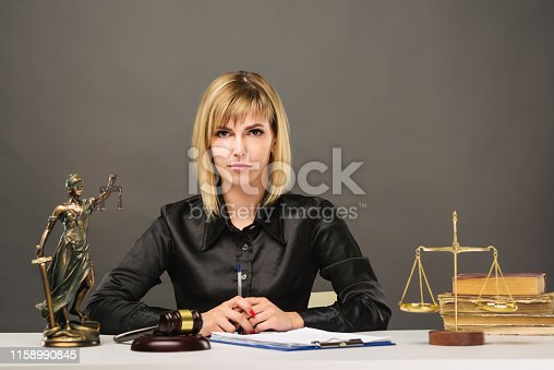 1070981872istockphoto A young fair woman judge works in her office. 1158990845