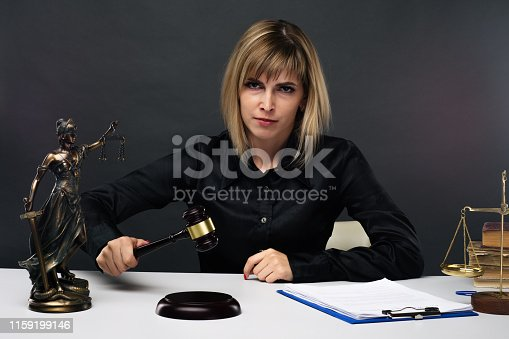 1070981872 istock photo A young fair woman judge works in her office. 1159199146