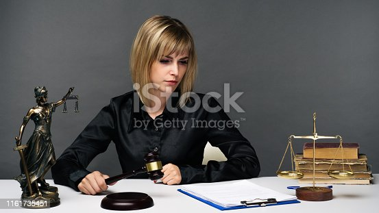 1070981872istockphoto A young fair woman judge works in her office. 1161735451