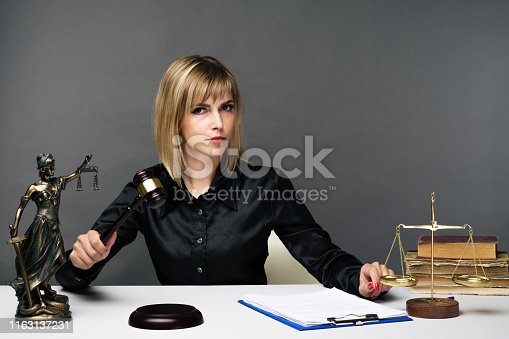 1070981872istockphoto A young fair woman judge works in her office. 1163137231