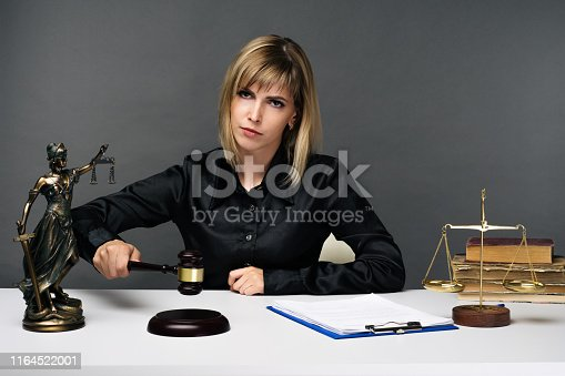 1070981872istockphoto A young fair woman judge works in her office. 1164522001