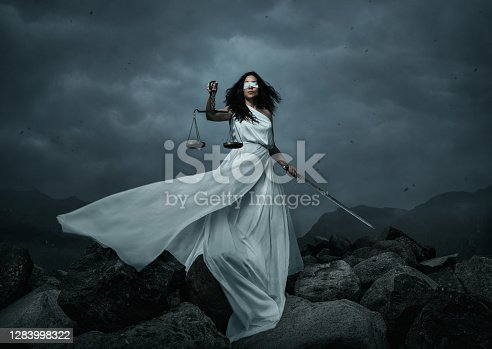 Young fairly woman with scale and sword over the dramatic sky with copy space