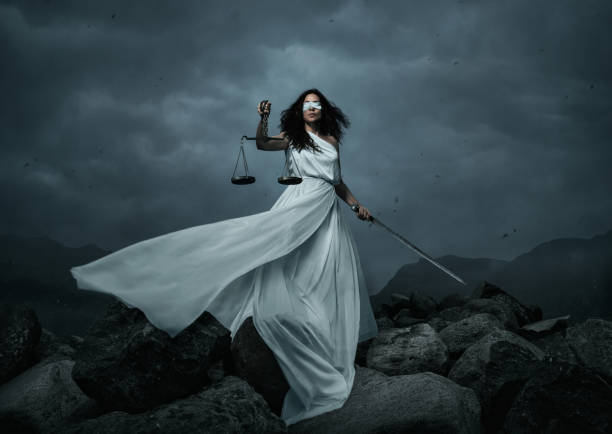 Young fairly woman with scale and sword over the dramatic sky stock photo