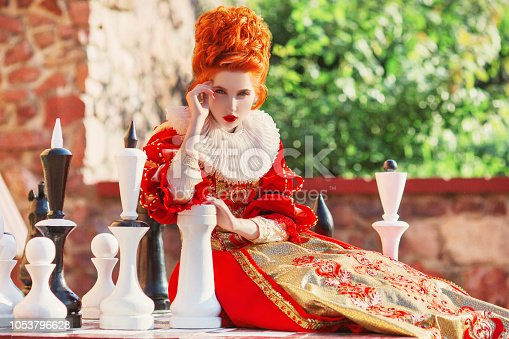 Young fairytale rococo queen with historical hairstyle is sitting on chess board. Renaissance princess play checkmate. Rococo queen in historical dress play chess. Think over the strategy checkmate