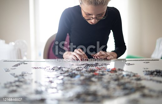 Young famale playing puzzle in Quarantine