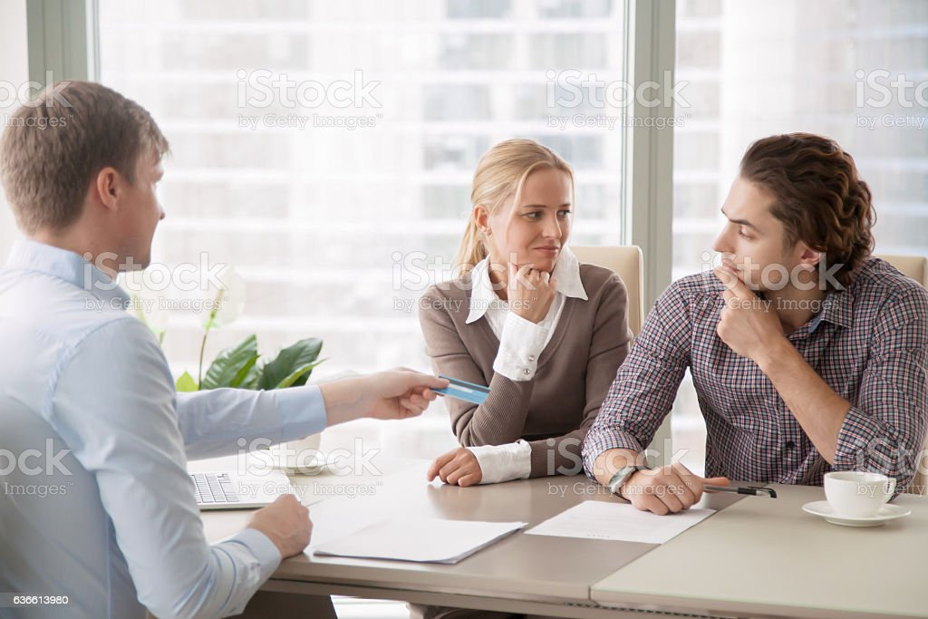 Young family and agent handing a credit card stock photo