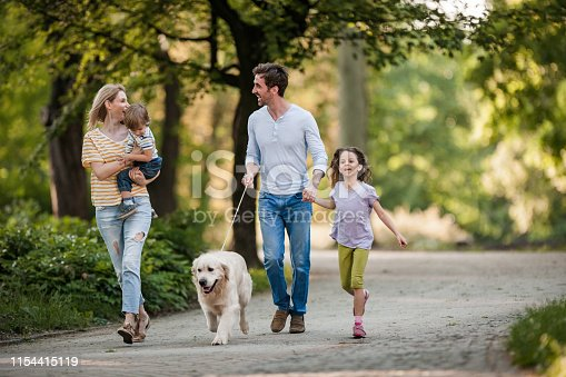 Happy family talking while walking with a dog in springtime at the park.