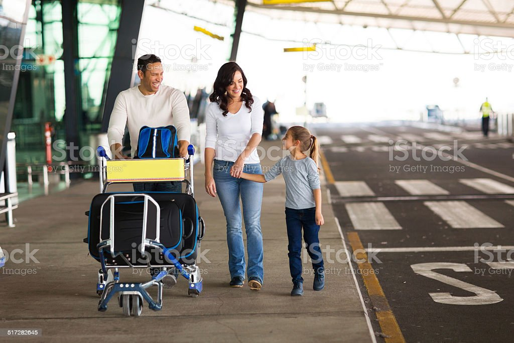 young family at airport with a trolley full of luggage stock photo