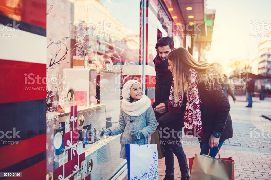 Family enjoying a window shopping for New Year and Christmas