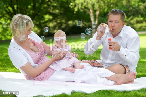 507271044istockphoto Young family blowing coloured soap bubbles with her baby girl 158396617