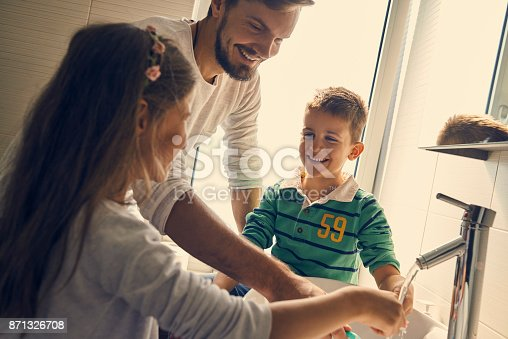 684029036istockphoto young family brushing teeth together and having fun 871326708