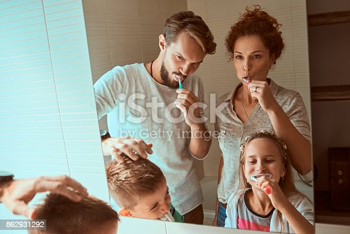 185211538istockphoto young family brushing teeth together 862931292