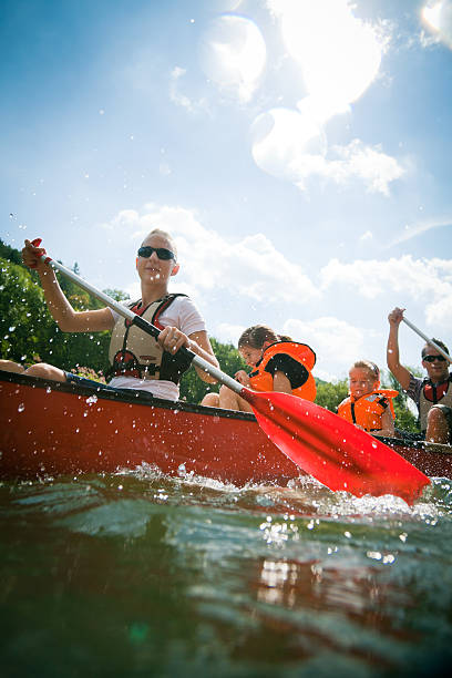 young family canoeing young family in a canoe on the neckar river in germany.  canoeing stock pictures, royalty-free photos & images