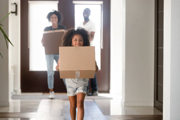 Young family carry boxes moving to new home Happy small African American girl holding cardboard box run into new house, young black family moving into bought apartment, excited daughter carry personal belongings to home. Relocation concept physical activity stock pictures, royalty-free photos & images