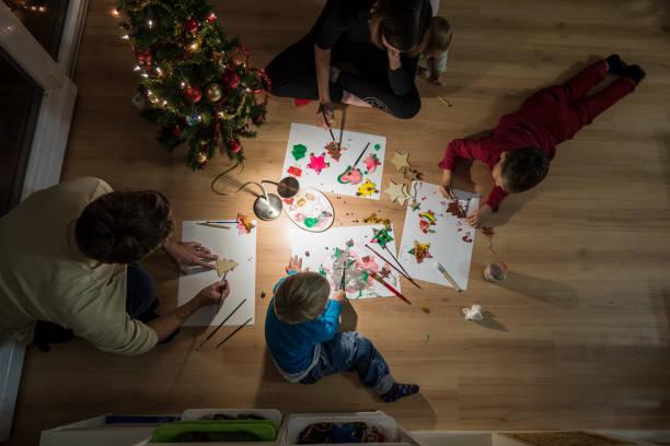 junge familie feiert weihnachten dekorationen - weihnachtsbilder zum ausmalen stock-fotos und bilder