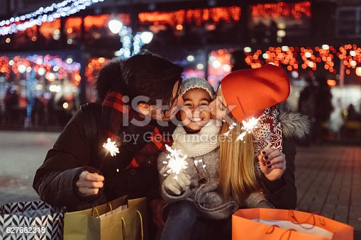 Cute couple with sparklers wishing Happy new Year to the little daughter
