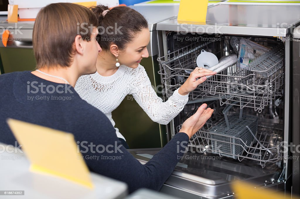 Ordinary young family choosing new dish washing machine in supermarket