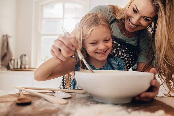 young family cooking in kitchen - kids cooking stock photos and pictures
