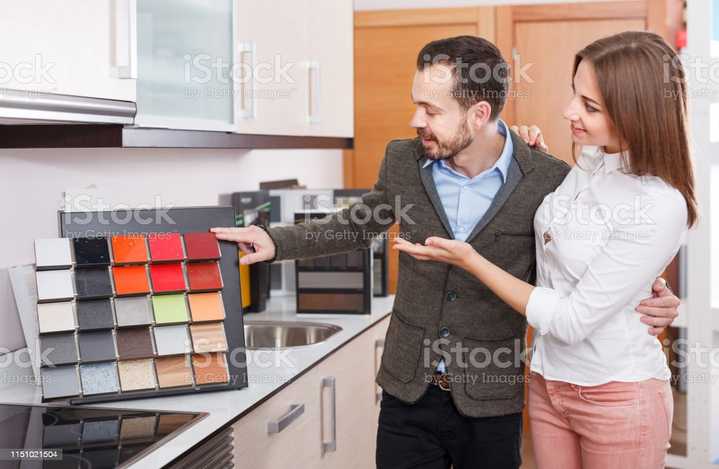 Young family couple choosing material for kitchen furniture in salon