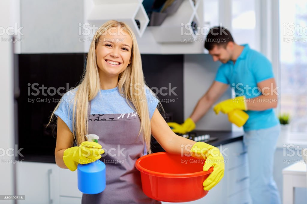 Young family couple doing cleaning in the kitchen stock photo