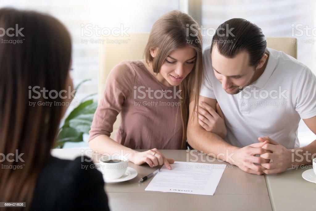 Jonge familie paar nemen lening, studeren contract overeenkomst vóór de ondertekening foto