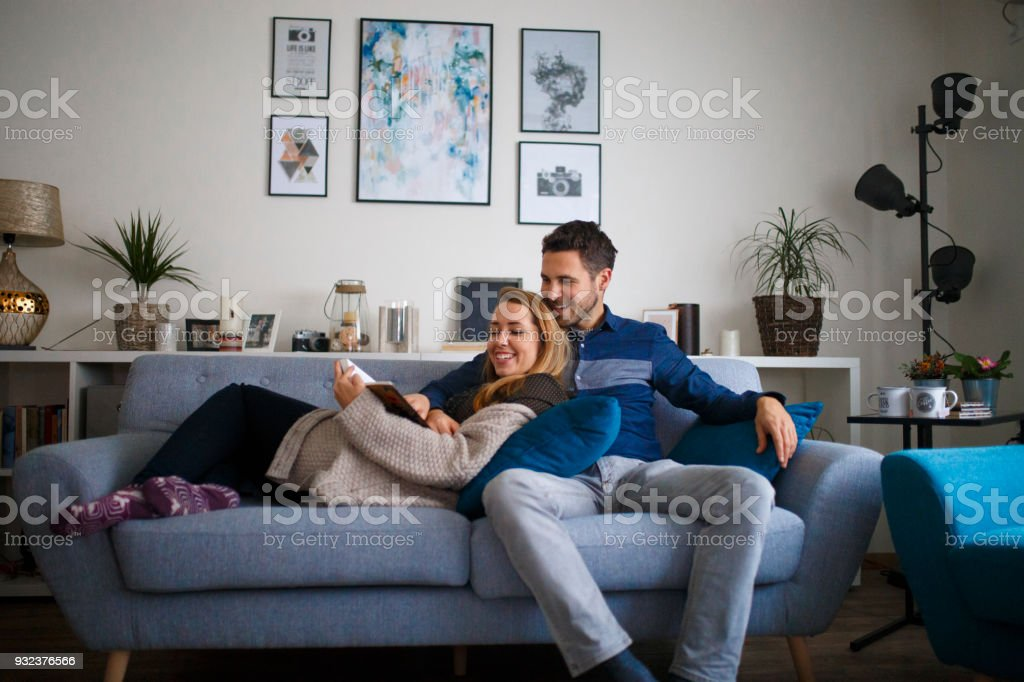 Young family couple together at home reading a book stock photo