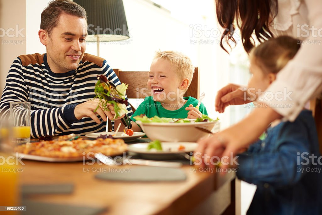 Joven familia comiendo en la mesa - foto de stock