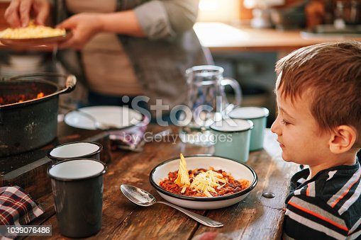 Young Family Eating Chili Con Carne in Domestic Kitchen