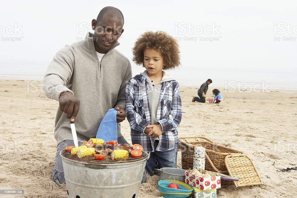 Young Family Enjoying Barbeque On Beach royalty-free stock photo