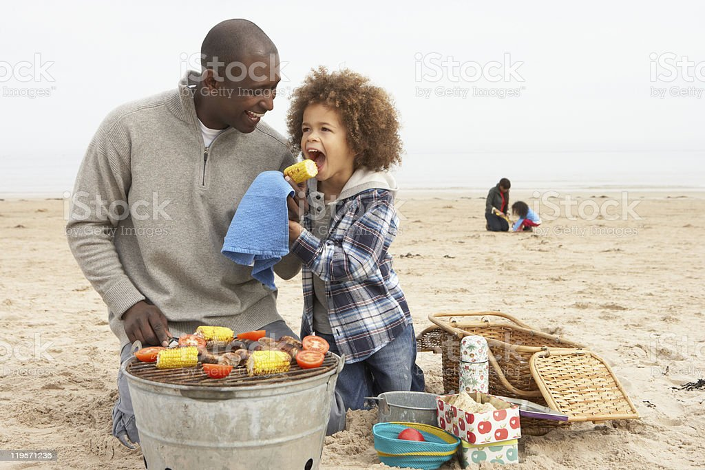 Young Family Enjoying Barbeque On Beach stock photo