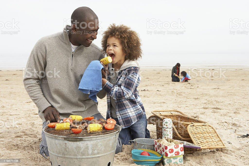 Jeune famille appréciant barbecue sur la plage - Photo