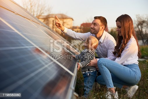 Side view shot of a young modern family with a little baby boy getting acquainted with solar panel on a sunny day, green alternative energy concept