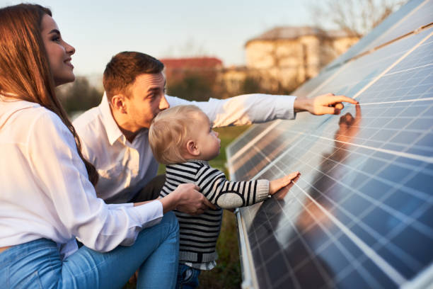 Young family getting to know alternative energy Side close-up shot of a young modern family with a little son getting acquainted with solar panel on a sunny day, green alternative energy concept solar panels photos stock pictures, royalty-free photos & images