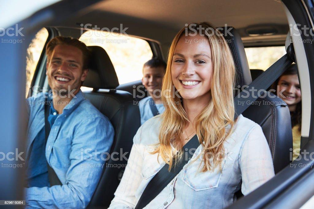 Familia va de vacaciones en un aspecto de coche a cámara - Foto de stock de 20 a 29 años libre de derechos