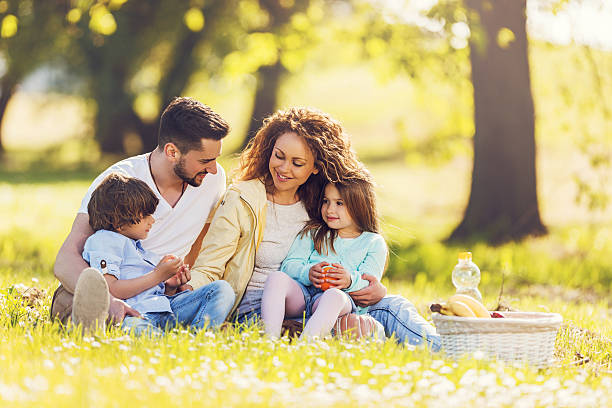 Junge Familie mit einem Picknick im Freien und Kommunikation. – Foto