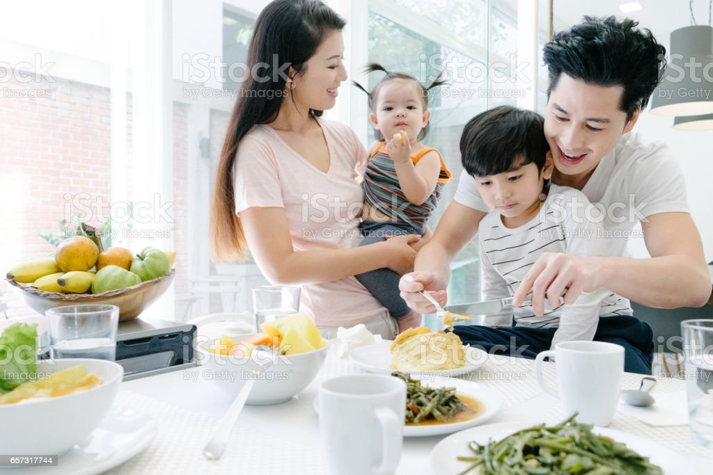 Young family having breakfast in the kitchen stock photo