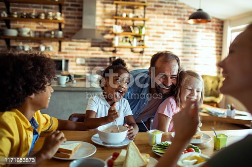 Close up of a family having breakfast and playing with each other