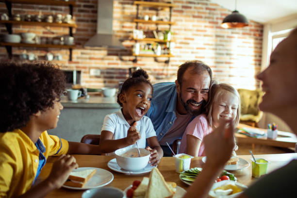 Young Family having Breakfast Close up of a family having breakfast and playing with each other mixed race person stock pictures, royalty-free photos & images