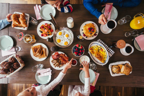 young family having breakfast with eggs, bacon, yogurt with fresh fruits - dining table stock photos and pictures