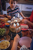 Young Family Having Delicious Chocolate Fondue in a Pot Served with Marshmallows