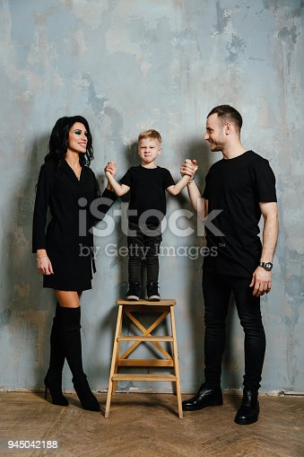 678651100 istock photo young family having fun at home on a background of a vintage textured wall 945042188