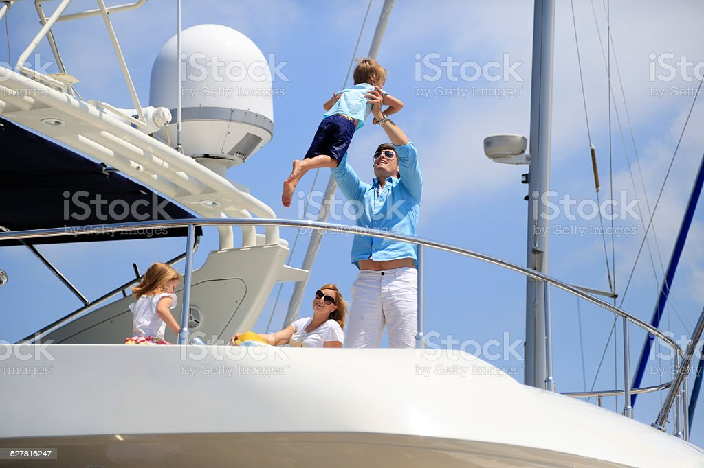Young family having fun on yacht stock photo