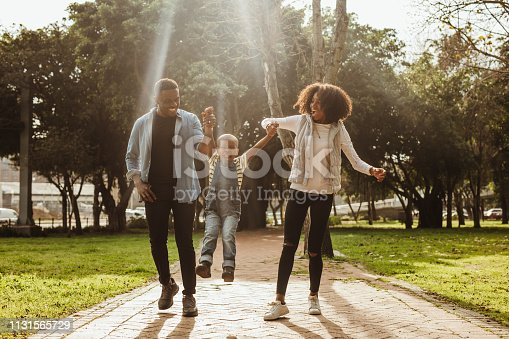Happy beautiful family of three walking in park. Happy couple in playful mood outdoors enjoying with their child.