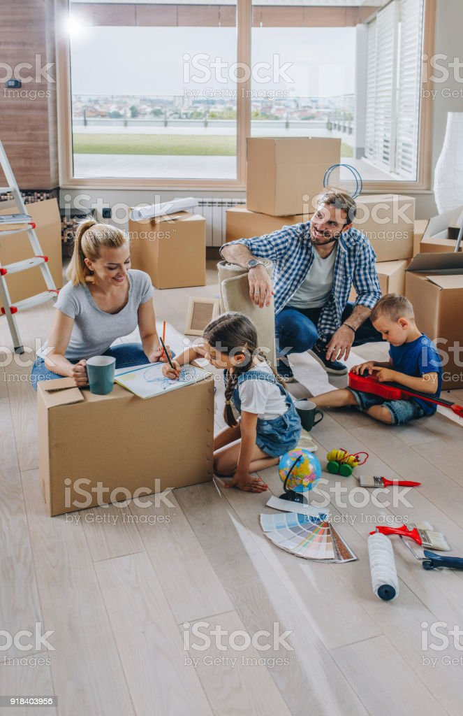 Young family having fun while moving into new apartment. stock photo