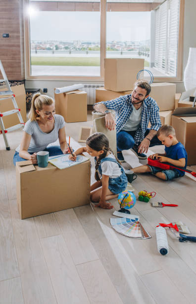 young family having fun while moving into new apartment. - happy mom packing some toys stock photos and pictures